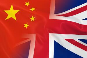 Chinese and British Relations Concept Image - Flags of China and the United Kingdom Fading Together